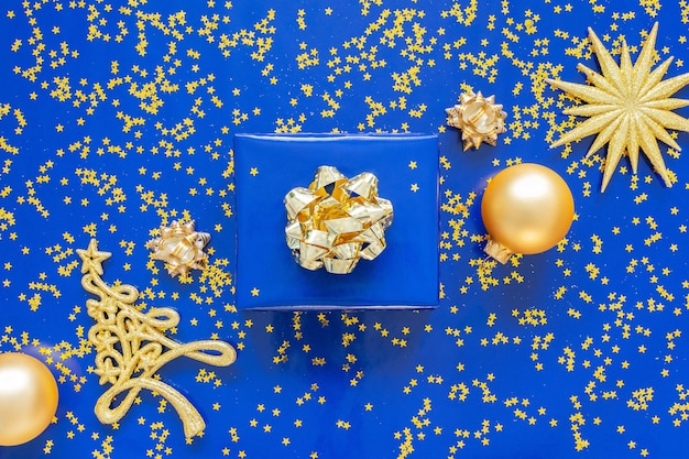 파란색 배경에 크리스마스 볼 황금 활과 전나무 트리, 파란색 배경에 황금 반짝 반짝이 별 선물 상자 프리미엄 사진