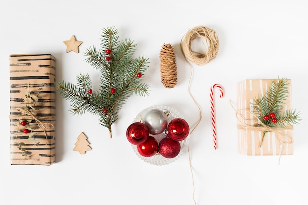 Gift boxes with fir tree branch and shiny baubles Free Photo