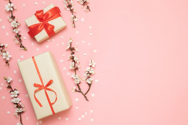 Gift boxes with red ribbons, flower branches Premium Photo