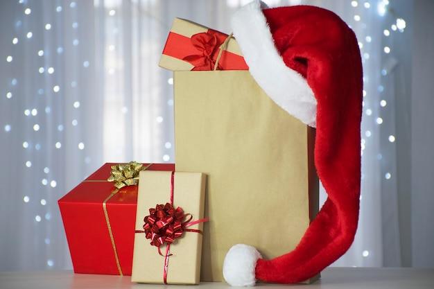 クリスマスライトのボケ味の紙袋の上にサンタの帽子が付いているギフトボックス Premium写真