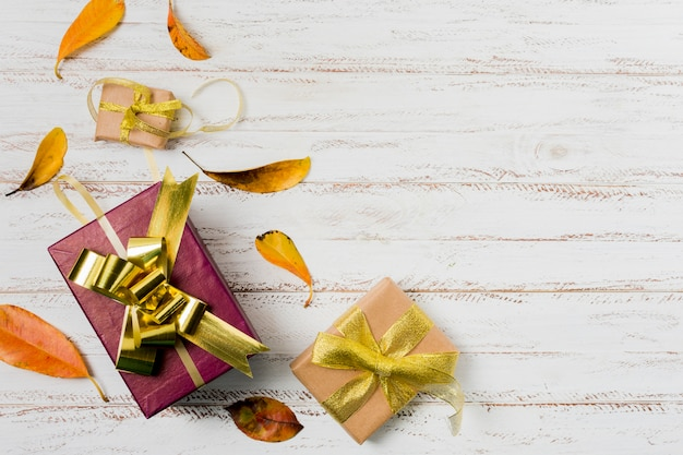 Gift boxes in wrapping paper with ribbons and autumn leaves on a white wooden background Free Photo