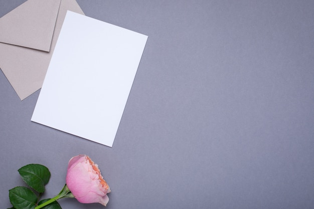 Gift card and envelope with pink rose on gray Premium Photo