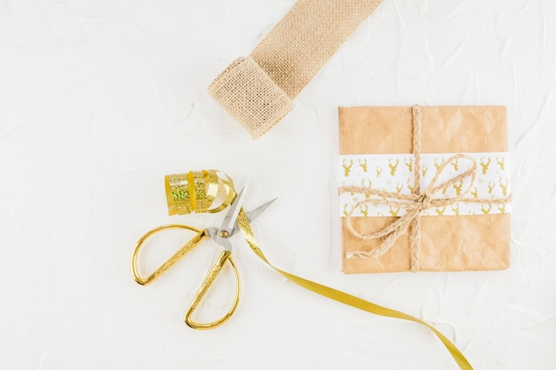 Gift in craft paper near scissors and ribbon Free Photo