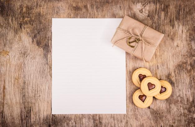 Подарок на день святого валентина, пустой лист бумаги, подарочная коробка и шоколадные сердечки Premium Фотографии