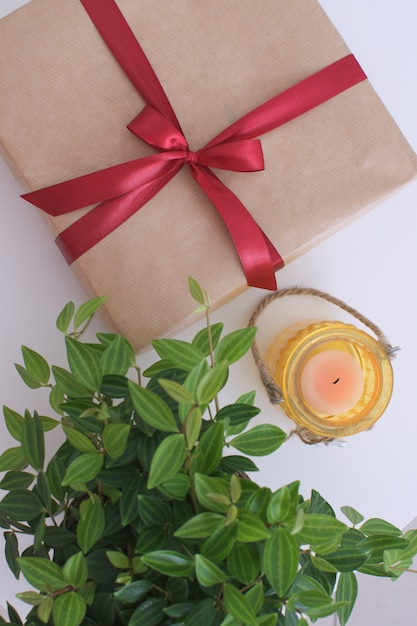 Gift  gift box on the table with green pland and candle birhday christmas new year Premium Photo