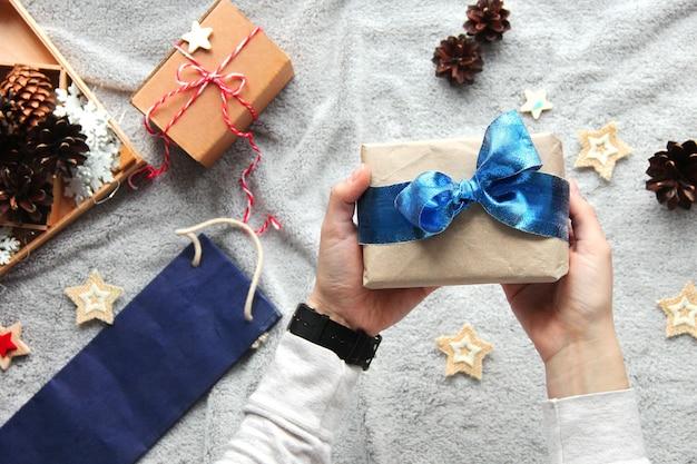 手に贈り物。ギフトラッピングプロセス。青い弓。クラフト紙のギフト。お祭りの雰囲気。 Premium写真