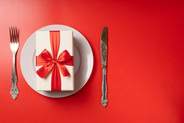 Подарок на сервировочной тарелке на красной стене Premium Фотографии