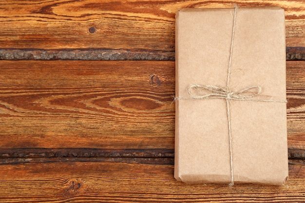 Gift packed in eco-friendly biodegradable cardboard on dark old wooden background with blank space for text Premium Photo