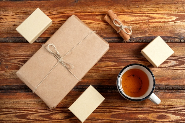 Gift packed in eco-friendly biodegradable cardboard and a glass of tea on a dark old wooden background with a blank space for text Premium Photo
