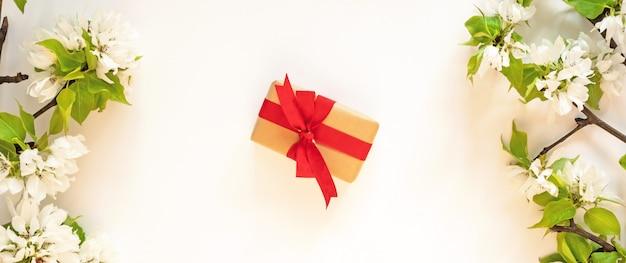 ギフトプレゼントボックス、リンゴの木の花の枝、白い壁のフラットが横たわっていた。花春の花赤いギフトボックスコンセプト Premium写真