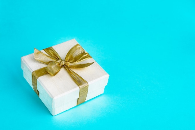 Gift or present box decorated with golden ribbon on blue background. top view, copyspace. birthday, mothers day, wedding, valentine day concept. Premium Photo