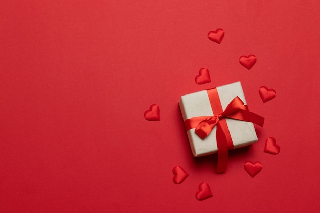 Gift or present box with red ribbon bow and love shape on red table.trendy composition for birthday, mother day or wedding. Premium Photo