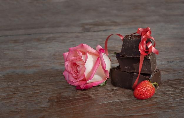 선물 세트 꽃, 초콜릿, 딸기. 장미와 나무 바탕에 딸기와 초콜릿 조각. 프리미엄 사진