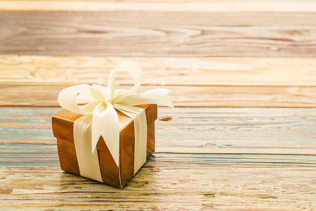 Gift with a white bow on a wooden table Free Photo