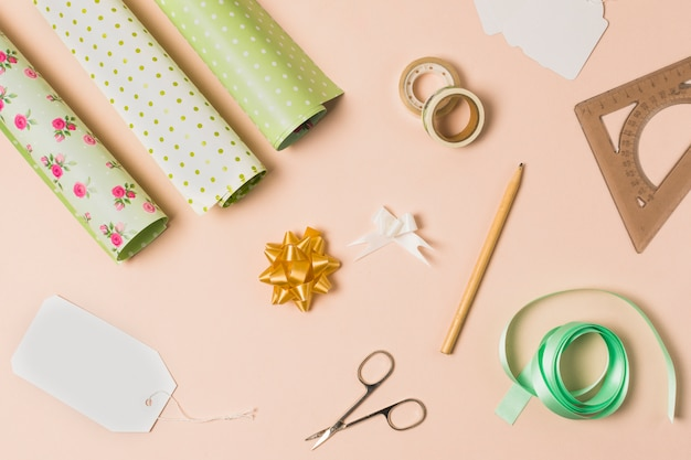 Gift wrapping material arranged over peach wallpaper Free Photo