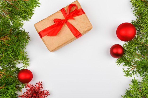 Подарочная упаковка с красным бантом на белом пространстве. хвойные зеленые ветви на белом пространстве. вид сверху. место для письма. рождественское пространство. Premium Фотографии