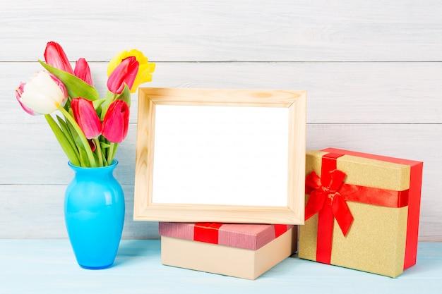 素敵な青い花瓶と明るい木製の背景にgiftboxesと空白のフォトフレームでカラフルな赤い春チューリップの花 Premium写真