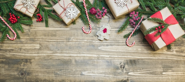 Gifts, holly berries and decoration on wooden board. Premium Photo