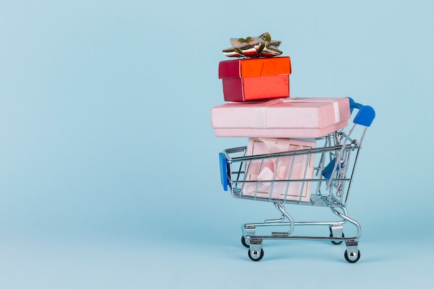 Gifts stacked in shopping card on blue surface Free Photo
