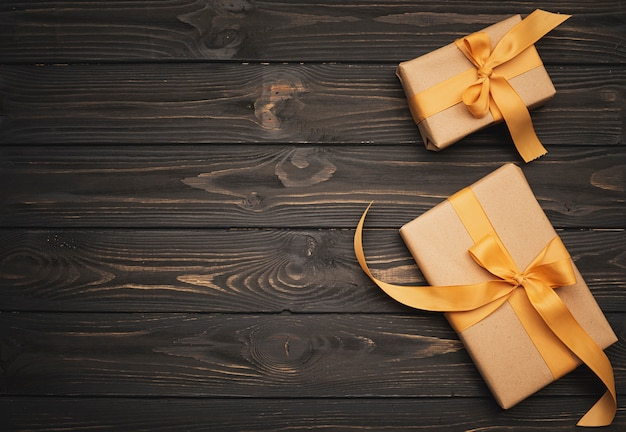 Gifts tied with golden ribbon on wooden background Free Photo