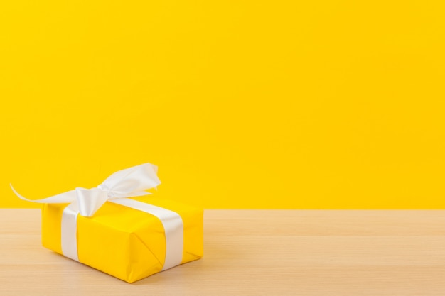 Gifts with ribbons on bright yellow background Premium Photo