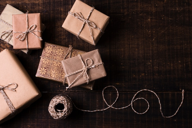 Gifts wrapped in paper with wooden background Free Photo