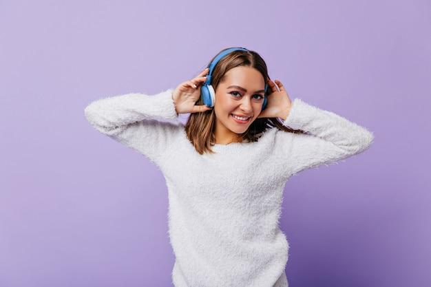 彼女のヘッドフォンに触れてかわいい気分の良い気分で笑う若い女性。短い黒髪の少女がライラックに喜んでポーズをとる 無料写真