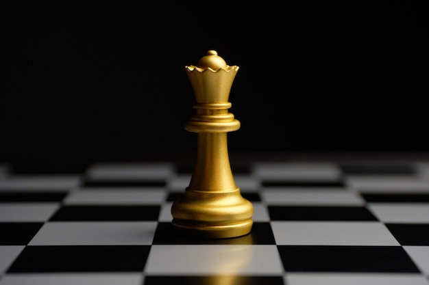 Gilded chess piece queen on the board. Premium Photo