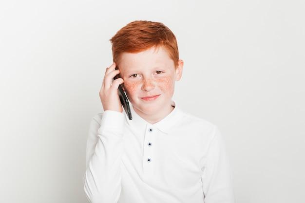 Ginger boy making phone call Free Photo