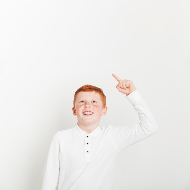 Ginger boy pointing up towards copyspace Free Photo