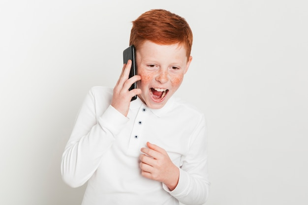 Ginger boy screaming while talking on smartphone Free Photo