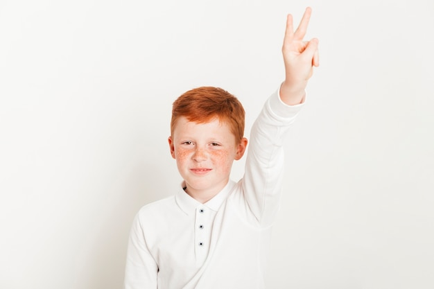 Ginger boy showing two fingers Free Photo
