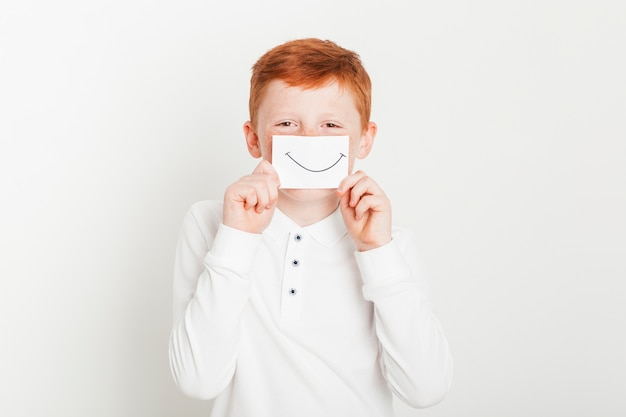 Ginger boy with card of smiling mouth Free Photo