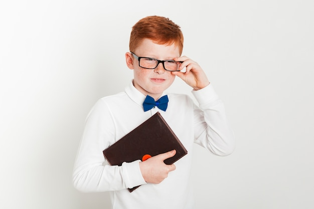 Ginger boy with glasses and book Free Photo
