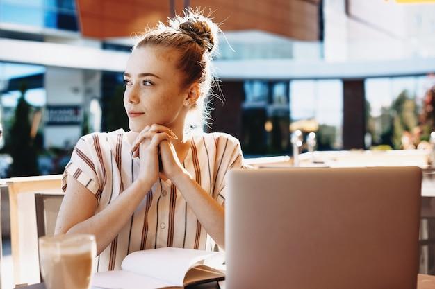 커피 숍에 앉아서 책과 칵테일로 컴퓨터에서 작업하는 동안 주근깨가있는 생강 백인 소녀 프리미엄 사진