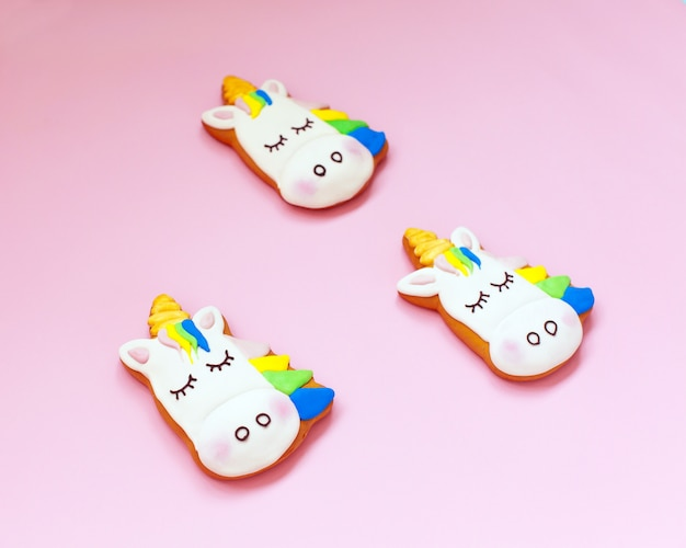 Ginger cookies in the shape of a unicorn on pink pastel Premium Photo