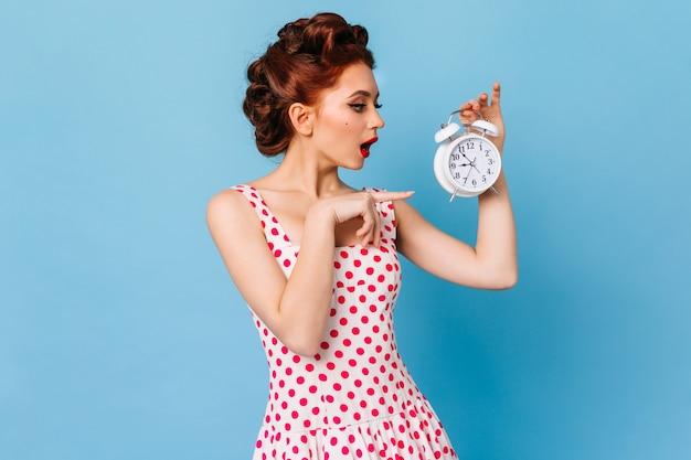 시계에서 손가락으로 가리키는 생강 우아한 소녀. 푸른 공간에 서있는 폴카 도트 드레스에 백인 여자의 스튜디오 샷. 무료 사진