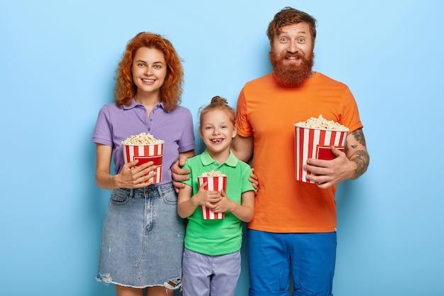 생강 가족은 영화관에서 자유 시간을 보내고, 재미있는 영화를보고, 행복하게 웃고, 맛있는 팝콘을 먹고, 서로 가까이 서고, 함께 즐기며, 즐겁게 지냅니다. 레저, 가족 시간 개념 무료 사진