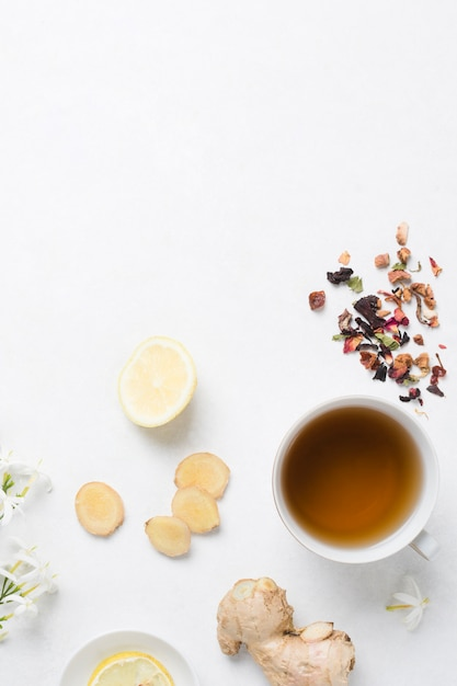 Ginger; lemon; herbal tea with dried herbs and jasmine blossom on white background Free Photo