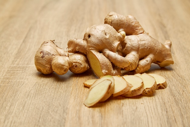 Ginger root sliced on wooden table Premium Photo