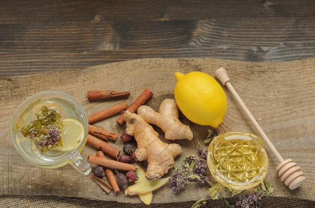 Ginger tea with lemon, herbs and cinnamon, alternative treatment for cold and flu Premium Photo
