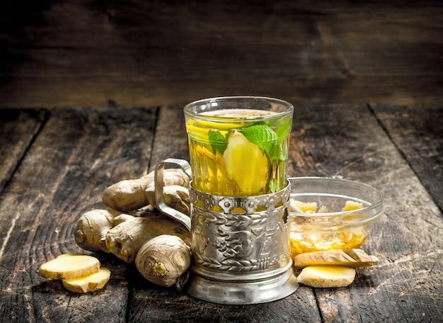ミントとレモンのジンジャーティー。木製の背景に。 Premium写真