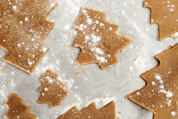 Gingerbread cookie. new year figures from a dough, prepared for baking in the oven. cookies in the form of christmas tree on paper for baking. christmas food concept. Premium Photo