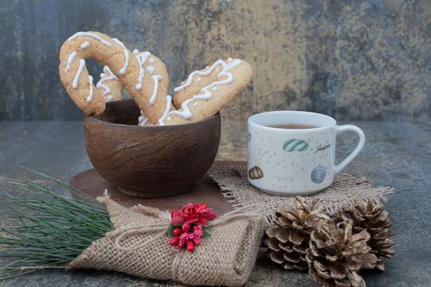 大理石のテーブルにジンジャーブレッドクッキーと松ぼっくりのお茶。高品質の写真 無料写真