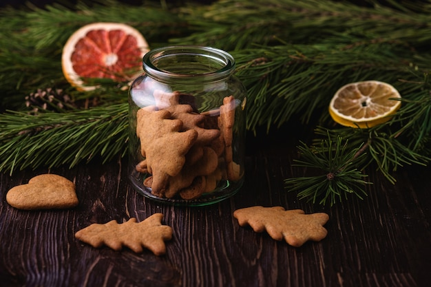 Gingerbread cookies christmas fir-tree and heart shape in glass jar on wooden table, citrus dried fruits, fir tree branch, angle view, selective focus Premium Photo