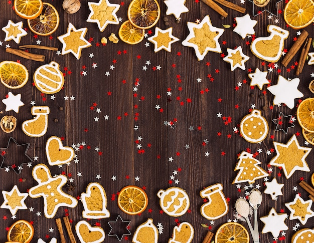 Gingerbread cookies christmas new year oranges cinnamon on wooden table with copyspace Free Photo