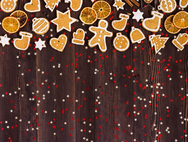 Gingerbread cookies christmas new year oranges cinnamon on wooden table Free Photo