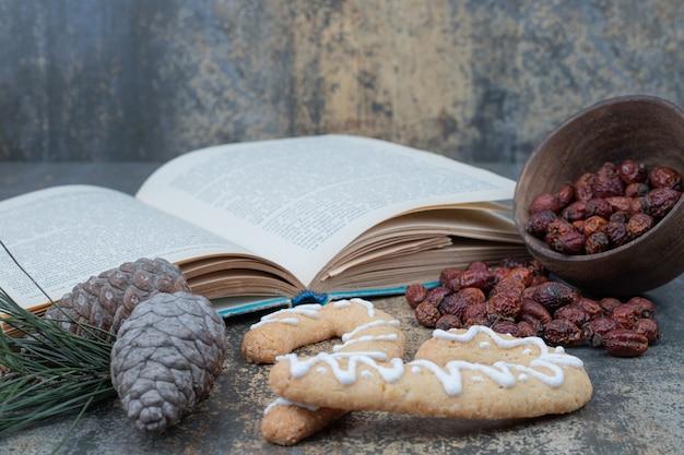 ジンジャーブレッドクッキー、乾燥したローズヒップ、大理石の背景に開いた本。高品質の写真 無料写真