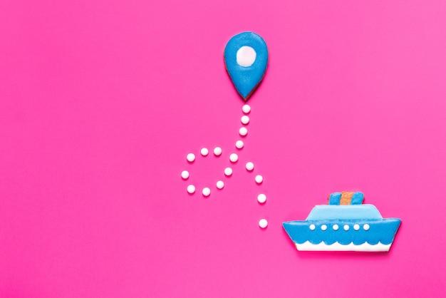 ジンジャーブレッドクッキーの船とピンクの背景のマップポイント Premium写真