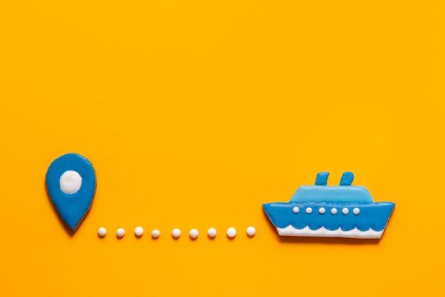 ジンジャーブレッドクッキーの船と黄色の背景上のポイントをマップ Premium写真